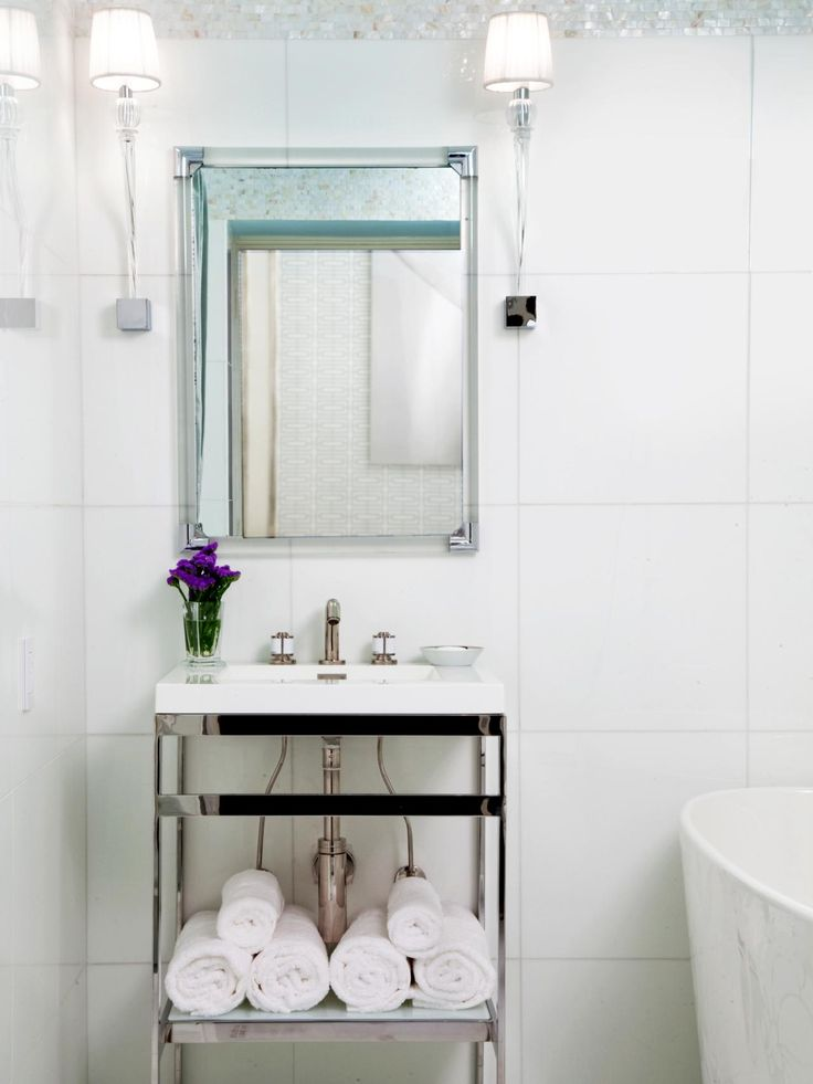 A dainty single vanity stores towels within reach of the bathtub. A small vase of royal purple flowers bring a pop of color and femininity to the crisp white bathroom.
