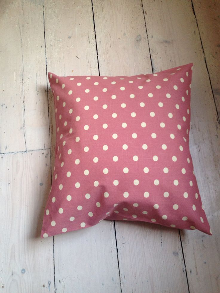 Pink polka dot homemade envelope throw pillow with bow fastenings covered with wooden buttons.