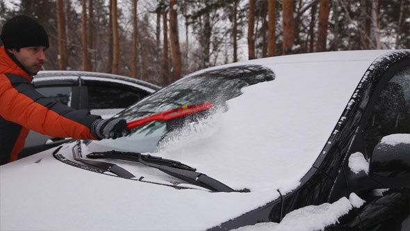 Man Cleans a Car from the Snow by Vinnikov78 Grey car stands amid pine forests or Park or alley. Car covered with fresh fluffy snow. A man cleans the windshield of the machine