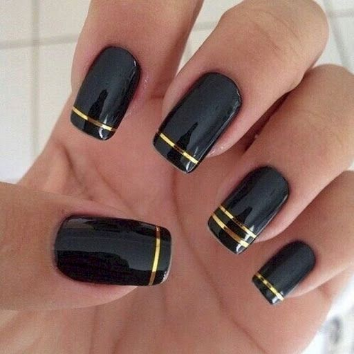 22 Black Nails That Look Edgy and Chic – Elegant gold striped nails.