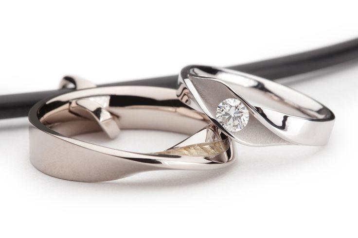De gerhodineerde witgouden damesring heeft een diamant die is gezet in een Orbit zetting waardoor de diamant vrijwel volledig is te zien. De scheen van de herenring tordeert. Hierbij komt het vlakje met zand op de vinger in beeld. De herenring wordt na de trouwplechtigheid aan een rubber collier gedragen in plaats van aan de hand. Aan het collier zit een getordeerde hanger waaraan de trouwring kan worden opgehangen.