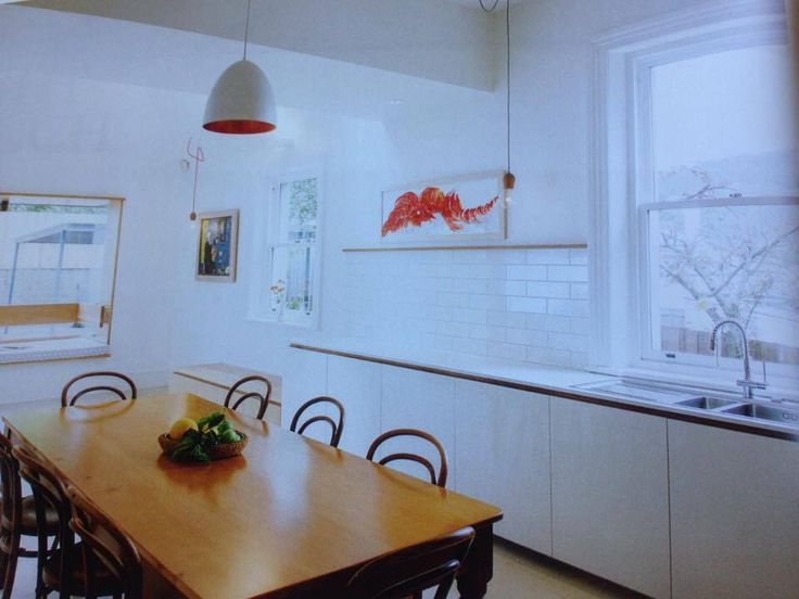 White counter / white joinery / timber feature behind cupboard finger pull