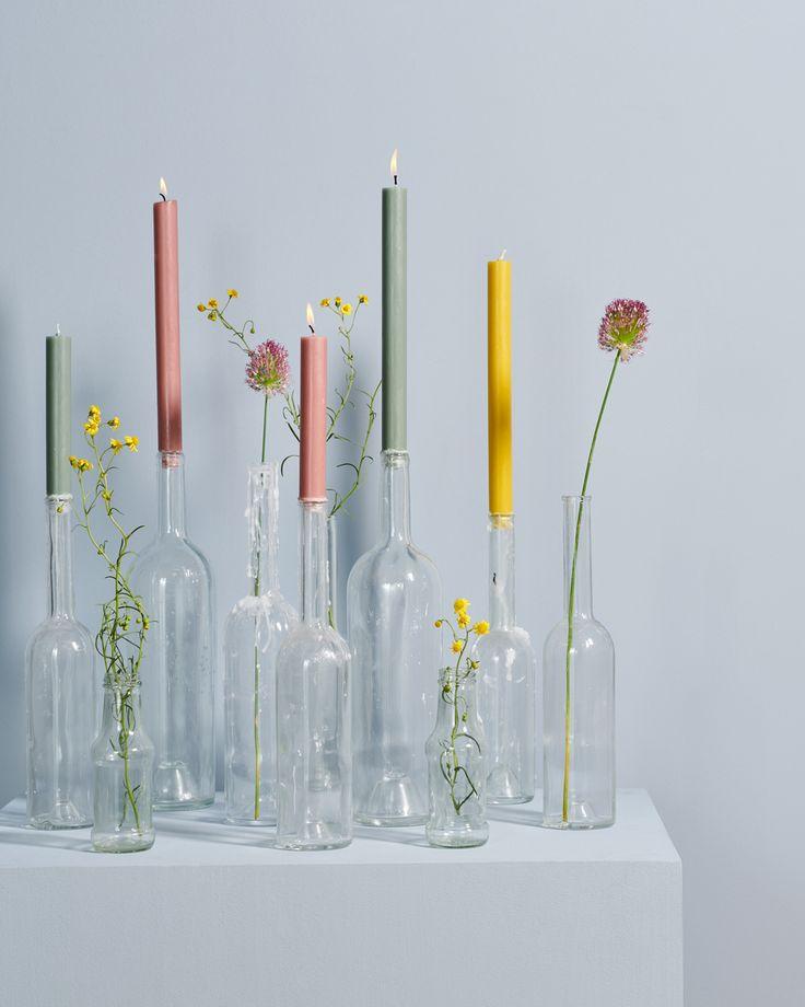 Kleurrijke kaarsen en bloemen in glazen