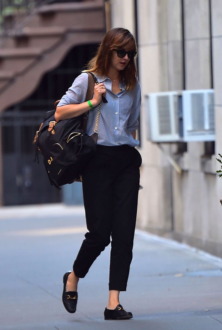 Dakota Johnson in an oxford shirt, cropped cigarette trousers, classic Gucci horsebit loafers and Burberry backpack.