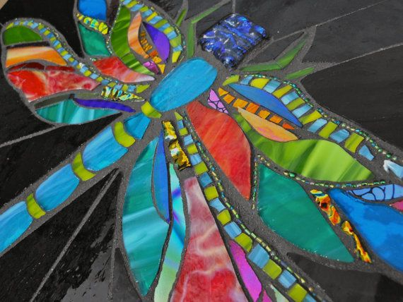 This jewel will fly right off into your daydreams. Beautiful jewel toned stained glass, dichroic glass, and beads light her up. Its light, 12x15 inches and can hang on any wall or plate stand.