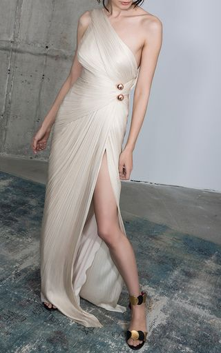 Rendered in silk tulle, this **Maria Lucia Hohan** one shoulder gown features a synched waist line, a metallic detail at the waist, and a draped skirt.