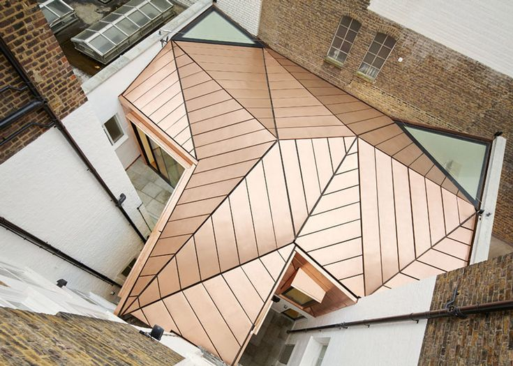 A faceted roof made from a shimmering copper-bronze alloy covers this house extension.