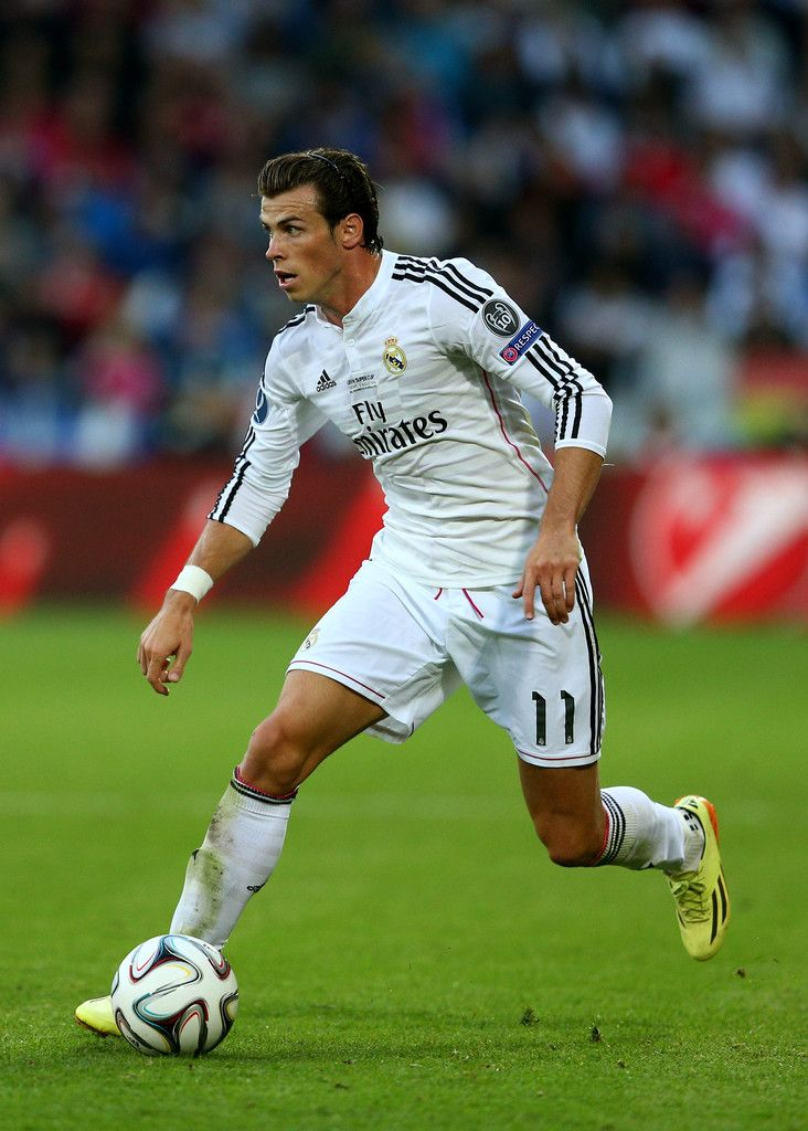Gareth Bale of Real Madrid runs with the ball during the UEFA Super Cup between Real Madrid and Sevilla FC at Cardiff City Stadium on August 12, 2014 in Cardiff, Wales.