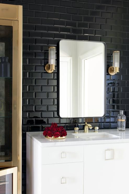 Glossy black subway tiles draw your attention to a…