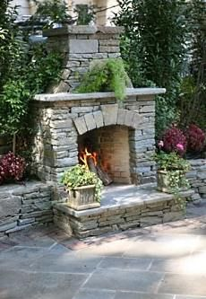 Natural stone patio and fire-place design by Landscape Aesthetics. It features  a  slightly arched firebox with a  prominent  keystone  centered  over the top of the opening. #patio #outdoors