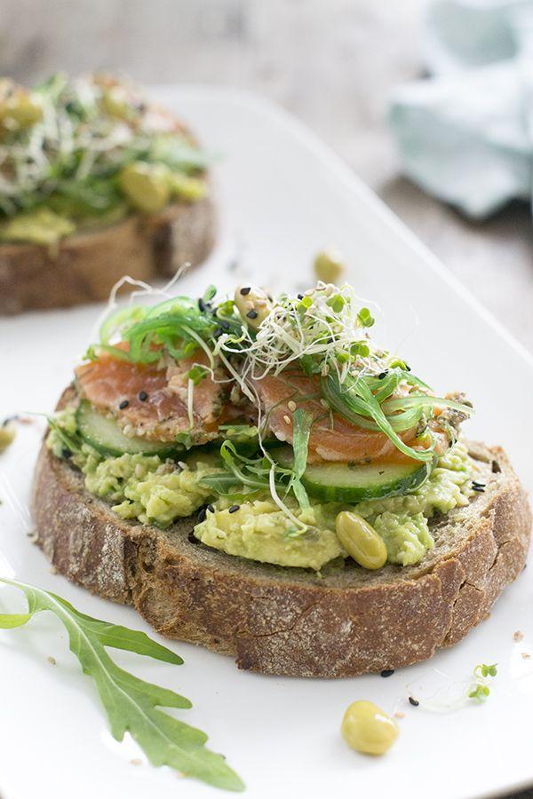 Poke toast met zalm! Lunchgerecht van verse ingrediënten. Knapperige toast met avocado, blokjes verse vis en extra toppings.
