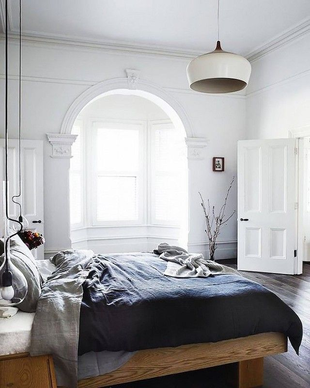 Minimalist bedroom with high ceilings, gray bedding, and a pendant light