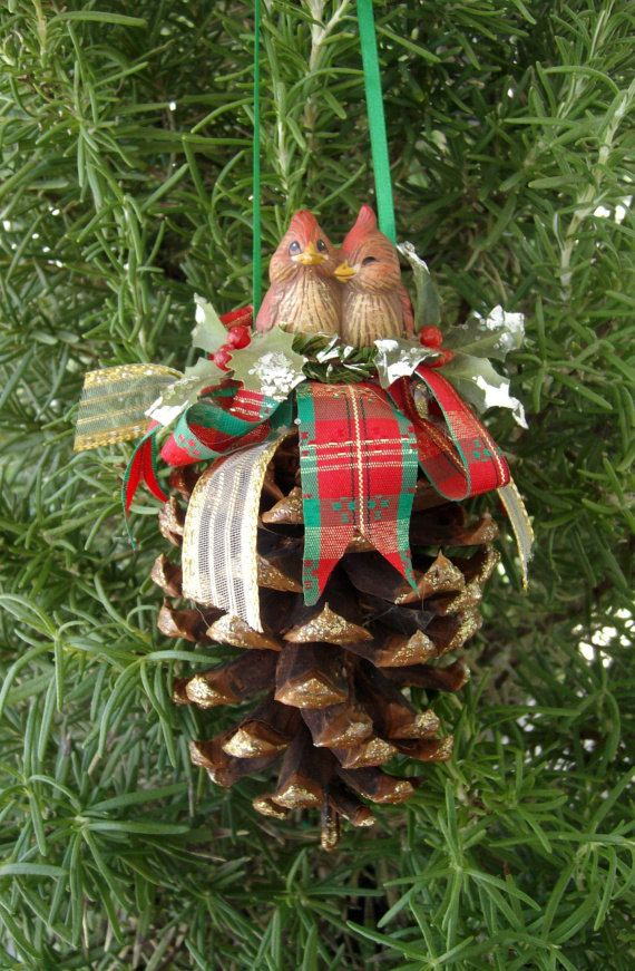 This natural pine cone is topped with a pair of hand painted miniature baby cardinals sitting in the middle of artificial holly leaves touched with
