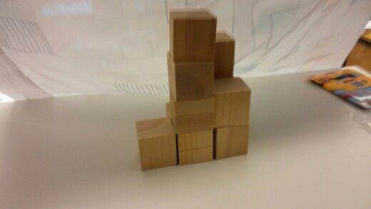 Luokassa isoilla kuutioilla malli, josta rakennetaan samanlainen pienemmistä palikoista. Oppilaat saavat käydä katsomassa mallia, mutta rakentaminen tapahtuu omalla paikalla.