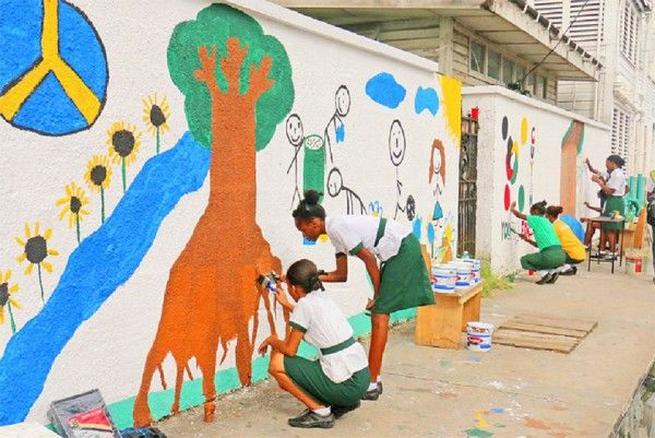 Art wall: Students of St Roses High in collaboration with Guyana Shines painting a mural on their school wall yesterday to depict keeping the environment clean among other positive messages. (Photo by Arian Browne)