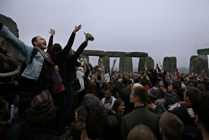 People dance and raise their hands in celebration during the summer solstice shortly after 04.52 am at the prehistoric Stonehenge monument, near Salisbury, England, Friday, June 21, 2013. Following an annual all-night party, thousands of new agers and neo-pagans waited at the ancient stone circle Stonehenge for the sun to come up, but cloudy skies prevented them. They danced and whooped in delight marking the summer solstice, the longest day of the year. (AP Photo/Lefteris Pitarakis)