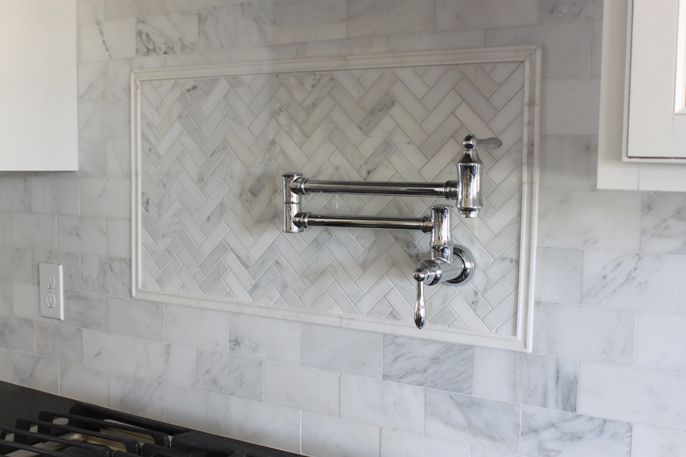 mixed metals kitchen - chrome and bronze with pot filler on herringbone white marble backsplash