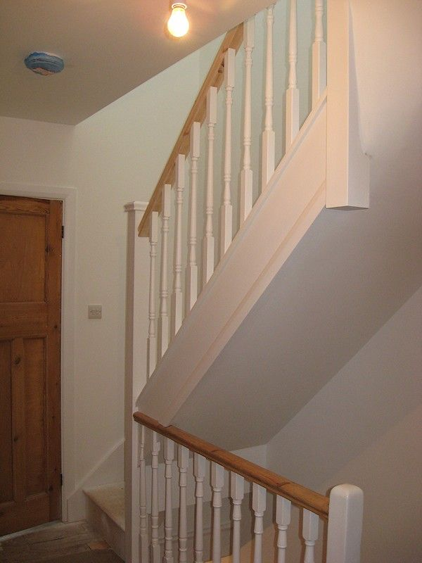 A softwood staircase for a loft conversion, painted white with feature pine handrail.