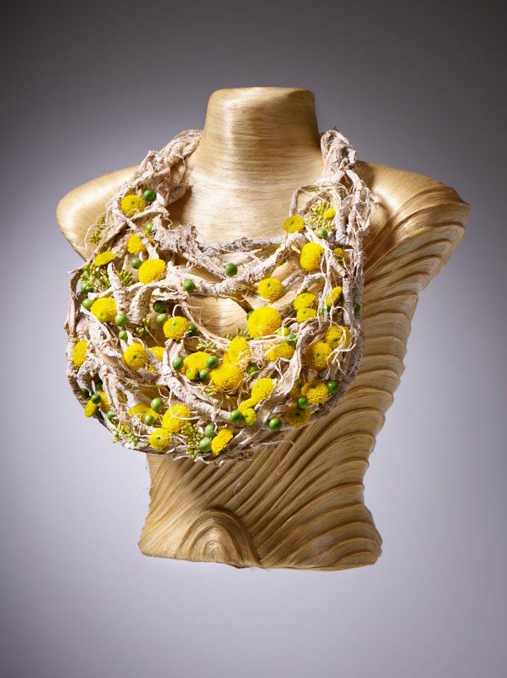 Pure & Nature! Atemberaubender floraler Halsschmuck mit Chrysanthemen-Blüten. Wie funkelnde Juwelen ist die Aurinko-Chrysantheme auf dieser Statement Kette in Szene gesetzt. Tragbar zu allen fließenden weichen Fashion-Stoffen ebenso wie zu einem enganliegenden Kleid.