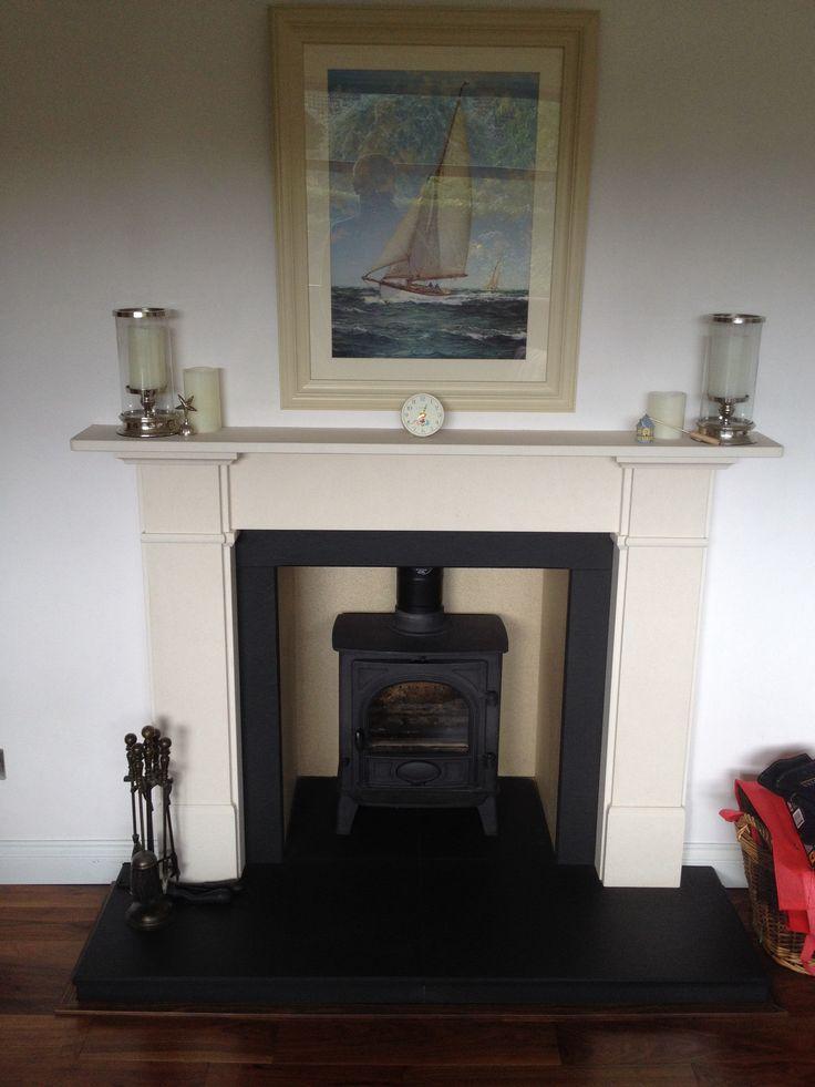 A log burner with a limestone fireplace, and a slate hearth