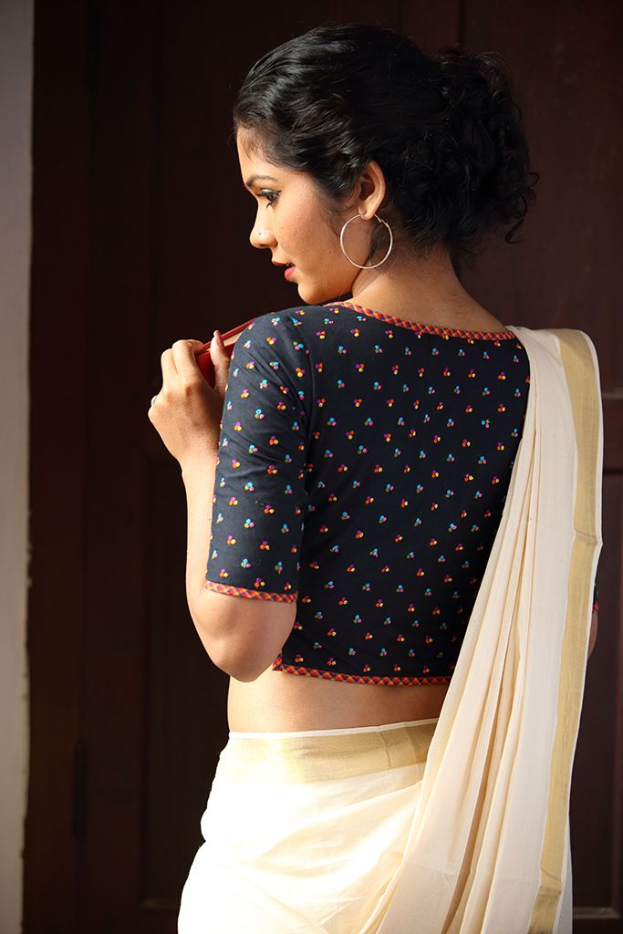 The Agnisakshi Blouse – Seamstress This blouse is our take on the iconic shirt blouse worn by fiery women writers and freedom fighters of Kerala. Classic and elegant like the women who wore them. The tiny coloured embroidery motifs on the soot black blouse add to its simple allure.