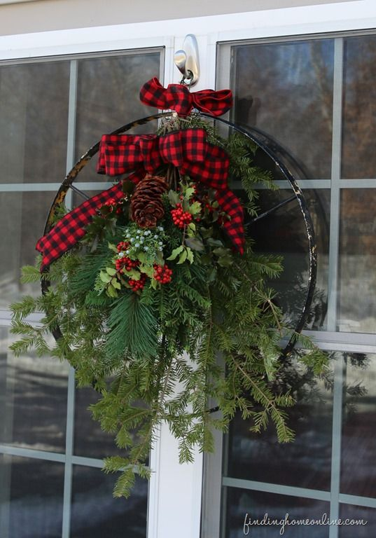 I just love this creative use of an old metal wheel decorated with greenery as a Christmas wreath! Finding Home