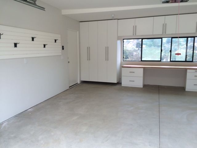 White Garage Cabinets With Two Butcher Block Work Benches And Slat Wall