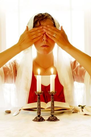 After lighting the Shabbat candles, the woman of the household covers her eyes and recites the traditional blessing over the candles.  They are lit no later than 18 minutes before sundown.