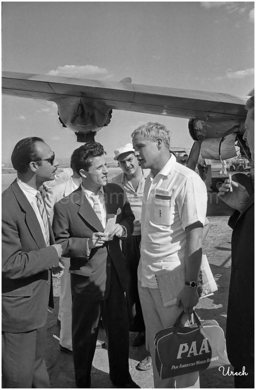 12 de julio de 1957 - Marlon Brando, recién desembarcado de su avión de Pan American World Airways, contesta a pie de pista las preguntas de los redactores, entre ellos, Yale, del diario Madrid. El actor, que llegó teñido de rubio por exigencias de su papel de soldado alemán en la película El baile de los malditos, estuvo pocos días en Madrid, de donde partió a Andalucía para disfrutar de unas vacaciones.