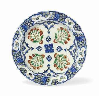 AN IZNIK POTTERY DISH   CIRCA 1565-70   With sloping cusped rim on short foot, the white interior painted in cobalt-blue, green and bole-red with four green and red floral sprays radiating around a central blue lobed medallion divided by blue arabesques, in a blue and black stylised wave and rock border, the reverse with paired blue tulips alternating with green and red flowerheads, drilled hole in rim and foot, negligible rim chips, otherwise excellent condition  11½in. (29.5cm.) d