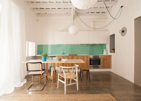 White and Wood Open kitchen green pop backsplash dining table as work surface. Spanish studio Nook Architects stripped out false ceilings and dividing walls to transform two next-door apartments in Barcelona's gothic quarter into a pair of bright and spacious homes (+ slideshow).