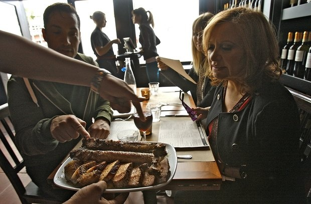 Chi Spacca: Diners Jeffrey Paul, Cindy Guagenti, center, and Caroline Manzo consider a platter of tomahawk pork chops.