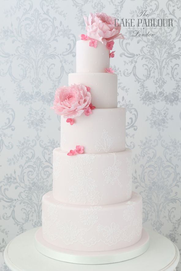 'PRETTY IN PINK' Wedding Cake - White 'cord lace' piped around the bottom tiers of a pale pink iced wedding cake decorated with sugar Peonies and Hydrangea petals.