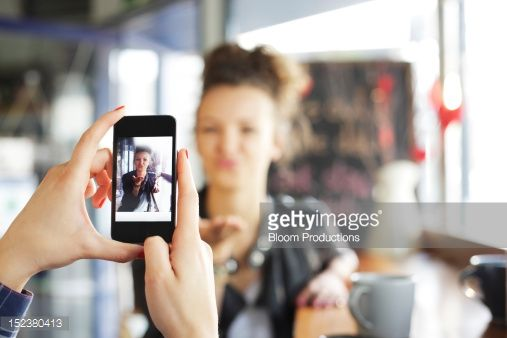 Foto de stock : girl taking a photograph of her friend