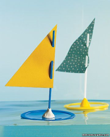 Homemade sailboat: Cut decorative paper into a right triangle, with the bottom shorter than the vertical edge. Punch three holes along vertical edge. Weave a drinking straw through the holes. Lodge the end of the straw into a ball of Play-Doh, and affix the sail to the top side of a coffee-can lid.