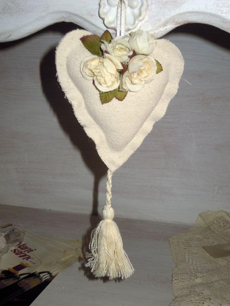 Cuore country fatto a mano, in tela grezza, con nappa. Roselline in tessuto avorio.  Completa di n.5 confetti in scatolina in PVC.
