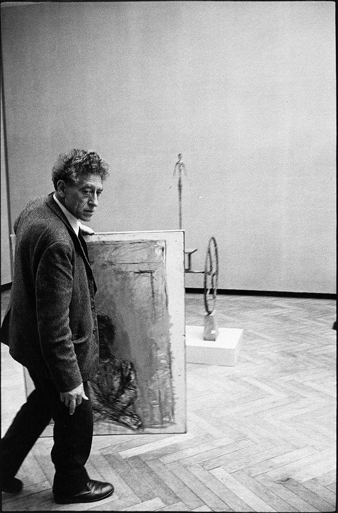 Ugo Mulas (Pozzolengo 1928 – Milano 1973), Alberto Giacometti con una sua tela, XXXI Biennale d'Arte, Venezia, 1962; cm 29,5 x 19,4 immagine, cm 29,8 x 19,9 foglio, Vintage. Stampa ai sali d'argento smaltata. © Ugo Mulas P. Castello 11