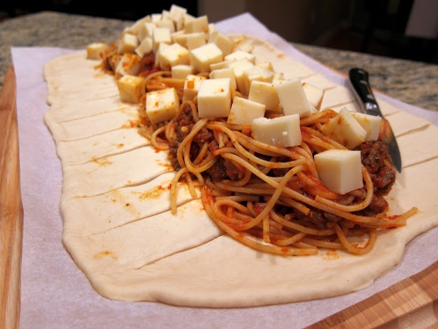 "1Loaf Bread Dough   6oz spaghetti,cooked   1c spag sauce   8oz mozz cheese,cut in1/2"" cubes   1egg  Parm cheese;Parsley flakes;garlic powder  Roll loaf12x16""on wax paper.Cover w/plastic wrap spag,drain wrap.Place noodles in 4""strip add sauce 1.5""apart w/in ½""of filling.Braid top strips toward filling.Braid left over right.Pull last strip over  under braid.Transfer to baking sheet.Brush w/egg white w/Parm,parsley,* 30min"