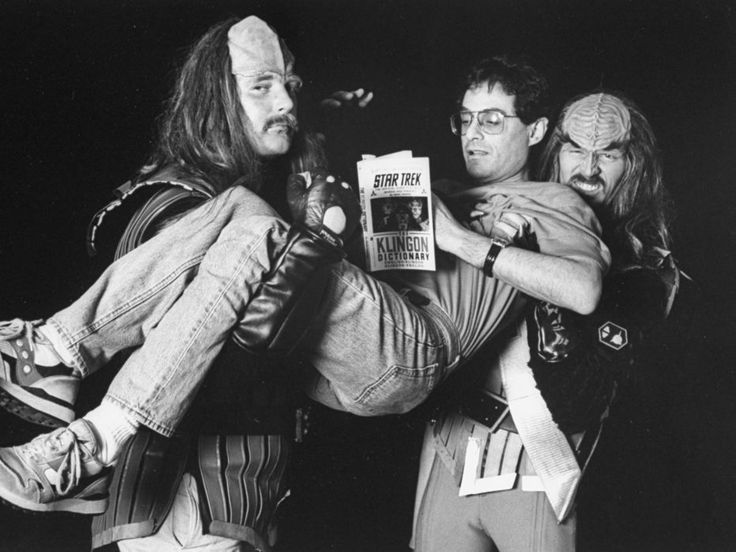 Author/lexicographer Marc Okrand, the creator of Klingon language for the Star Trek TV series, being bodily carried by two men made-up & wearing costumes as Klingons while reading his book THE KLINGON DICTIONARY at the Air & Space Museum. (Photo by Robert Sherbow/The LIFE Images Collection/Getty Images)