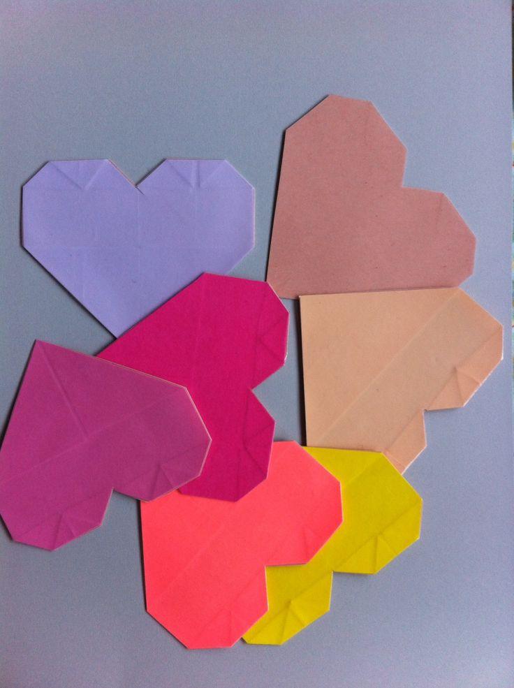 Origami onderzetters. Vouw een aantal origami harten, plak ze op een karton. Lamineer het karton en knip de harten uit.
