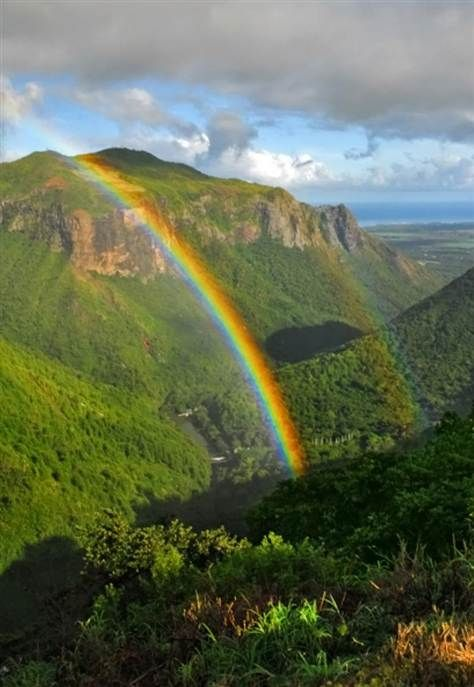 A rainbow arcs over Tamarind Valley, Mauritius Island. Note the double rainbow to the right of the primary one.