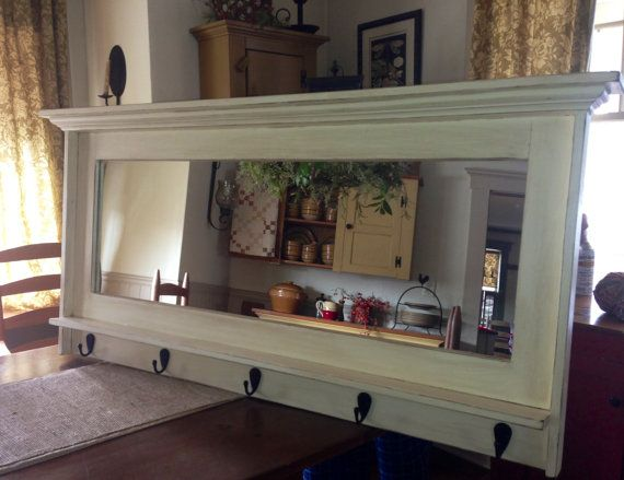 This coat rack entryway mirror is made of all pine with bed moulding lining the top. It features a small shelf and 5 matte black coat hooks. Mirrors like this are our specialty and can be made to order in different sizes and configurations so send us a message or request a custom order.