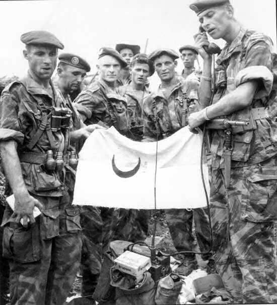 Paras of the French Foreign Legion showing captured FLN flag and equipment in Algeria.