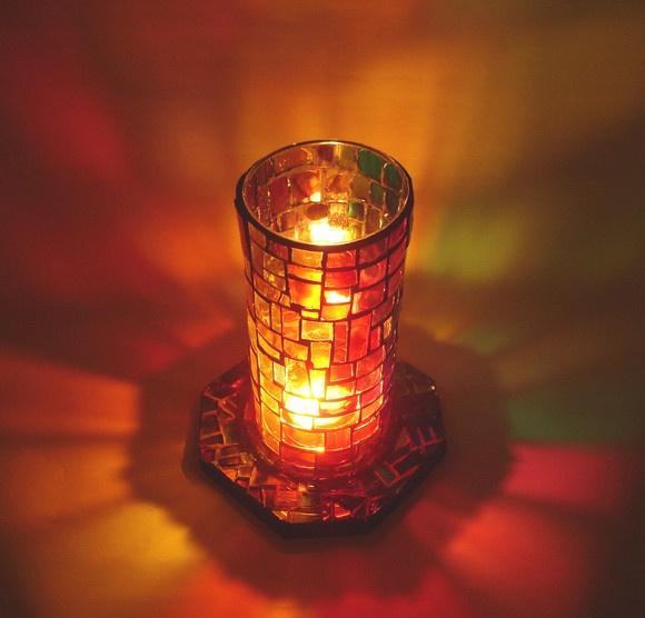 Luminária confeccionada a partir da reutilização de vidros e madeira.  Corpo de vidro revestido por vidros coloridos artesanalmente formando degradê arco-íris. Base em madeira, formato octagonal, com aplicação de vidros coloridos nos mesmos tons do cilindro e pequenos pedaços de espelho.  Belíssimo efeito de projeção de cores quando acesa.  Acompanha uma vela votiva. R$86,00