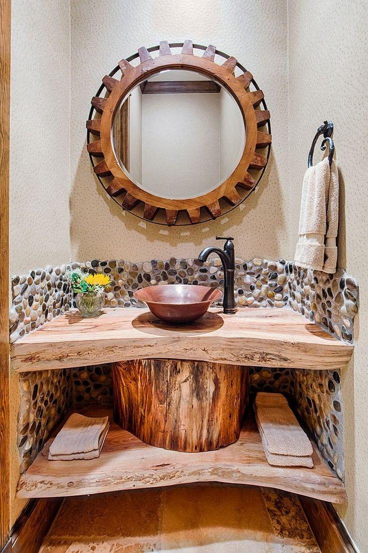 petite salle de toilette de style rustique aménagée avec un plan vasque bois brut, un miroir soleil en bois et décorée d'une mosaïque en galets