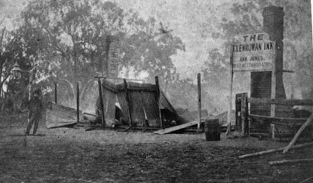 """This photograph shows the burnt remains of the Jones's Hotel, the scene of the final confrontation between Ned Kelly and the Victorian Police. A sign still stands: """"The Glenrowan Inn, Ann Jones, best accommodation""""."""