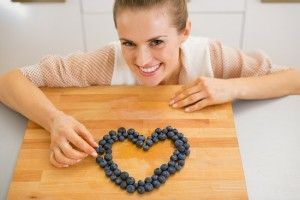 woman-making-heart-with-blueberries