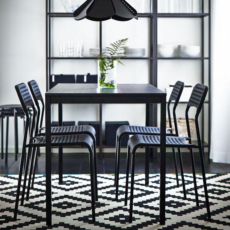 Svart matbord med svarta stolar och en svartbrun förvaringskombination