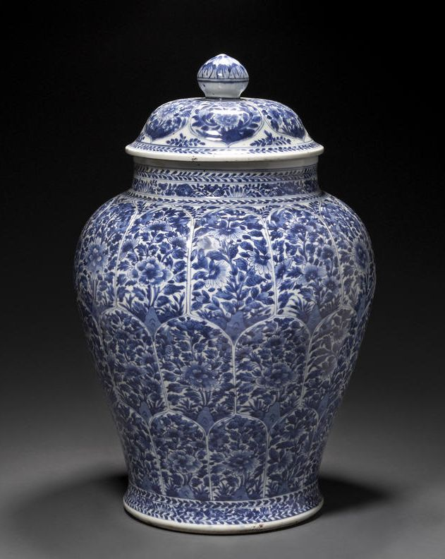A blue and white porcelain covered jar  Kangxi period  Thickly potted with a short neck and ovoid body that spreads outward toward an unglazed, rounded foot pad and recessed base, the exterior walls painted with three tiers of reserves filled with densely leafed flowering branches above floral and leaf bands that repeat around the neck and the edge of the domical cover with further floral reserve panels encircling the lotus bud finial.