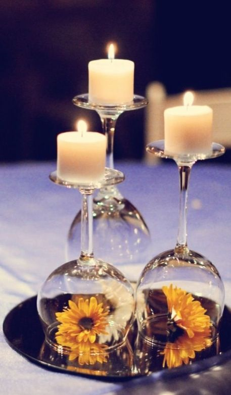 For a bride on a budget -  wine glasses with a flower inside them and a candle on top. Looks amazing